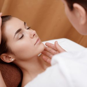 Professional consultation. Beautician examining the face of a young female client at spa salon